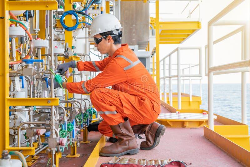 Instrumentera pumpen för membranen för underhållsteknikerfixande den kemiska på den frånlands- plattformen för fossila bränslenwe arkivbilder