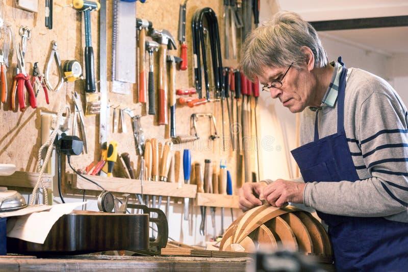 Instrumentera tillverkaren som snider kroppen av en luta arkivbild