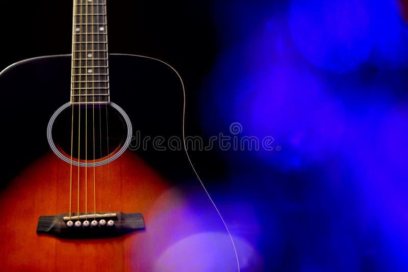 Instrumento acústico de la guitarra con el fondo azul fotografía de archivo