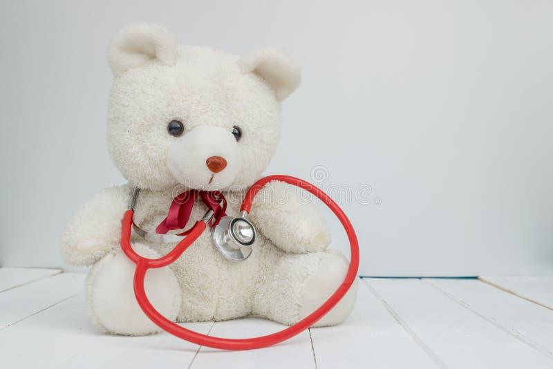 Instrumento branco do doutor da posse do urso da boneca foto de stock