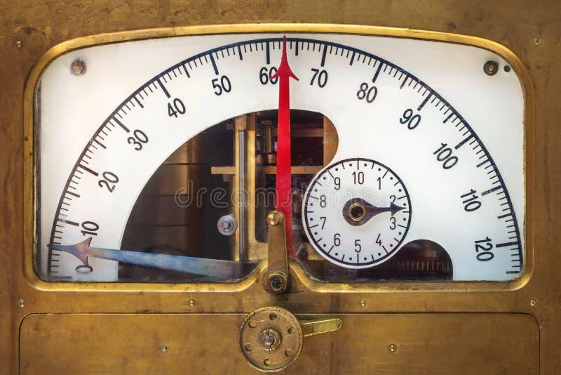 Instrumento de la medida del vintage con un indicador rojo de la aguja imagen de archivo libre de regalías