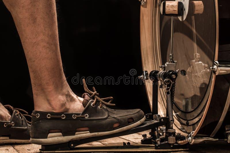 instrumento de percussão, bombo com o pedal na placa de madeira com fundo preto, o pé dos homens imagens de stock