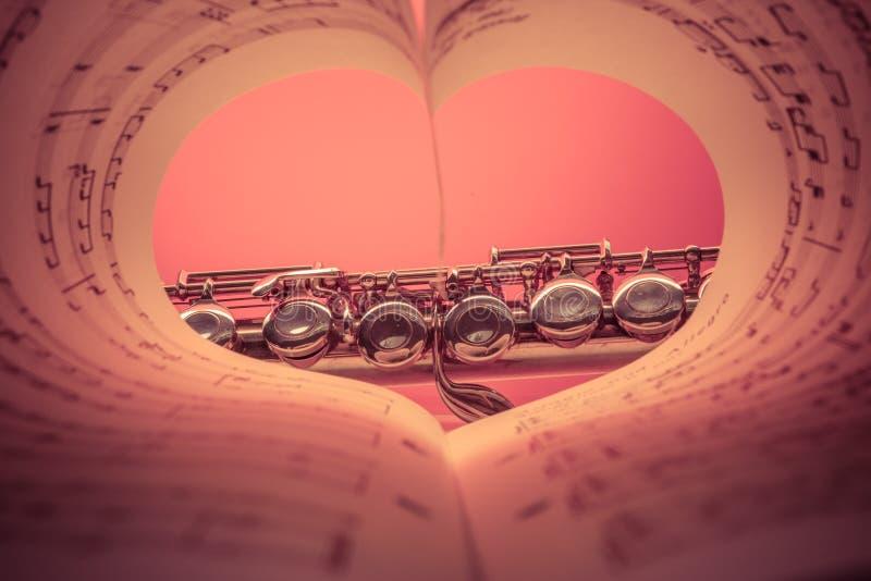 Instrumento musical de Chrome visto no livro dado forma coração da contagem da música foto de stock royalty free