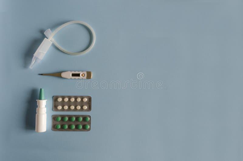 Instrumento nasal colocado plano da lavagem, termômetro eletrônico e de mercúrio, gotas nasais e pulverizador, comprimidos da gri foto de stock