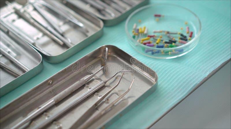 Instrumentos dentales de acero, espejo, en un fondo azul Instrumentos dentales foto de archivo