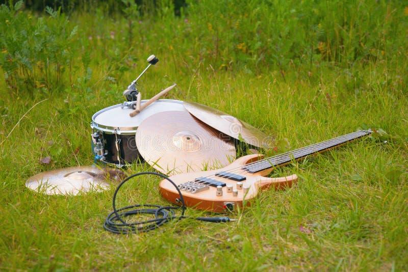 Instrumentos musicais, guitarra, cilindro, placas na grama imagem de stock
