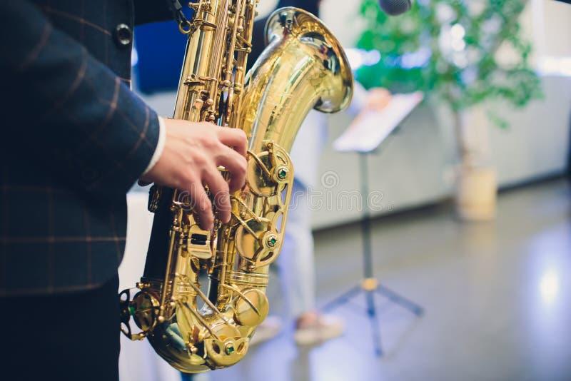 Instrumentos musicais, saxofonista das mãos do jogador de saxofone que joga a música jazz Close up do instrumento musical do saxo imagem de stock