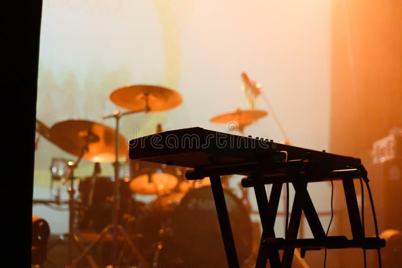 Instrumentos musicales en el escenario llenos de luz naranja imagen de archivo libre de regalías