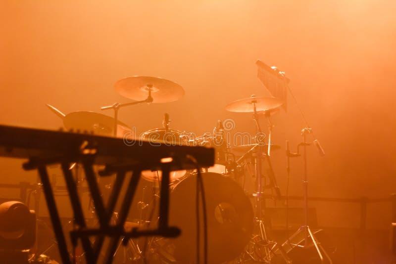 Instrumentos musicales en el escenario llenos de luz naranja foto de archivo