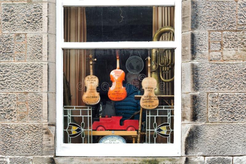 Instrumentos musicales viejos en la ventana de un segundero y tienda de antigüedades en el pueblo de Malvinas en Escocia fotografía de archivo