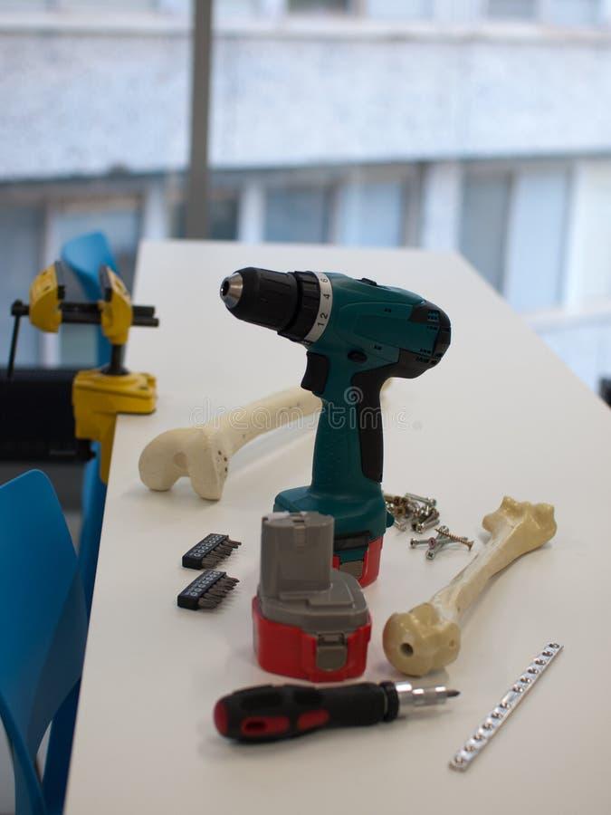 Instrumentos y huesos plásticos para las cirugías ortopédicas que entrenan para los doctores jovenes y los estudiantes de medicin imágenes de archivo libres de regalías