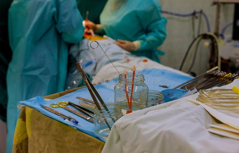 Instruments chirurgicaux sur la table pour l'opération avec des collègues exécutant la pièce en fonction de travail photo stock