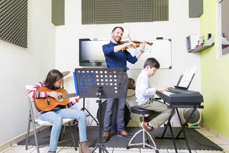 Instruments d'And Pupils Playing de professeur divers dans la classe images stock