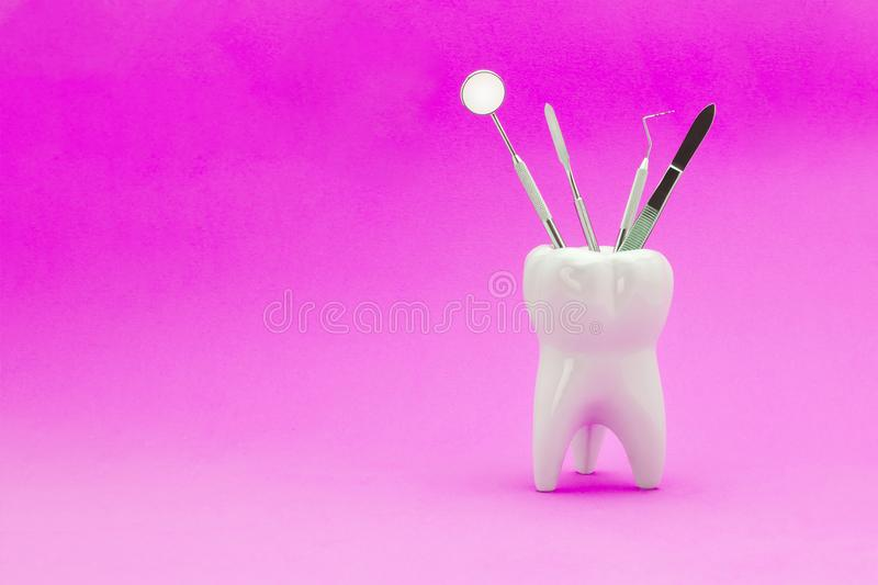 Instruments of the dentist mirror tweezers probe forceps stand i. N the support as a human tooth on a blue background. Procurement of copy space and text royalty free stock photography