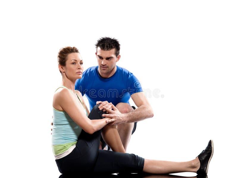 Instrutor aeróbio do homem que posiciona o exercício da mulher foto de stock