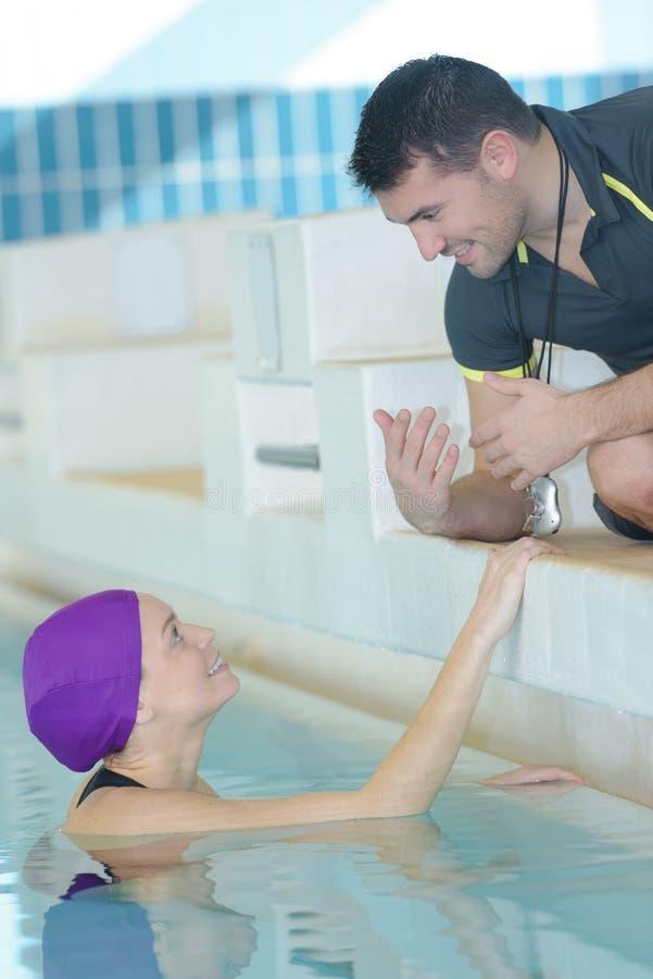 Instrutor apto que fala ao nadador no centro do lazer imagens de stock