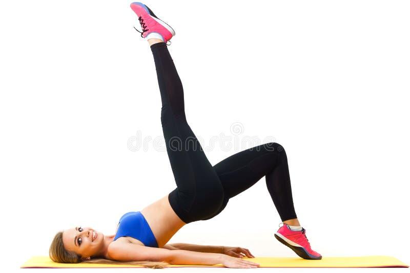 Instrutor bonito que dá certo com a esteira da ioga no branco imagem de stock royalty free