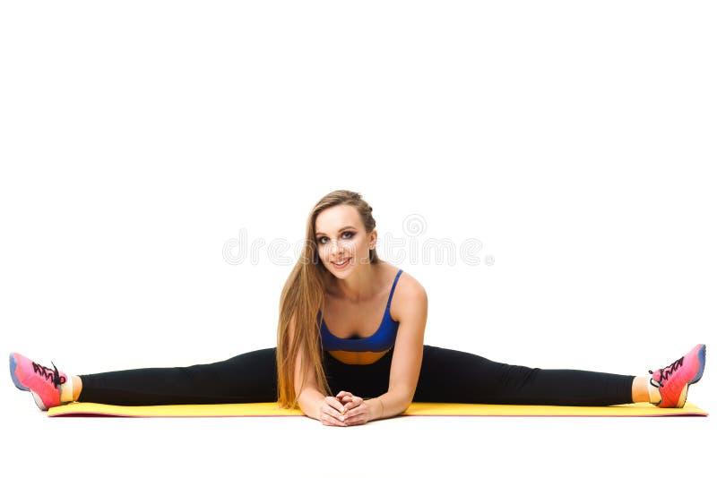 Instrutor bonito que dá certo com a esteira da ioga no branco fotografia de stock