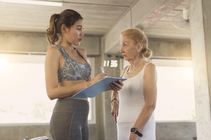 Instrutor com a mulher superior no centro de reabilitação imagens de stock