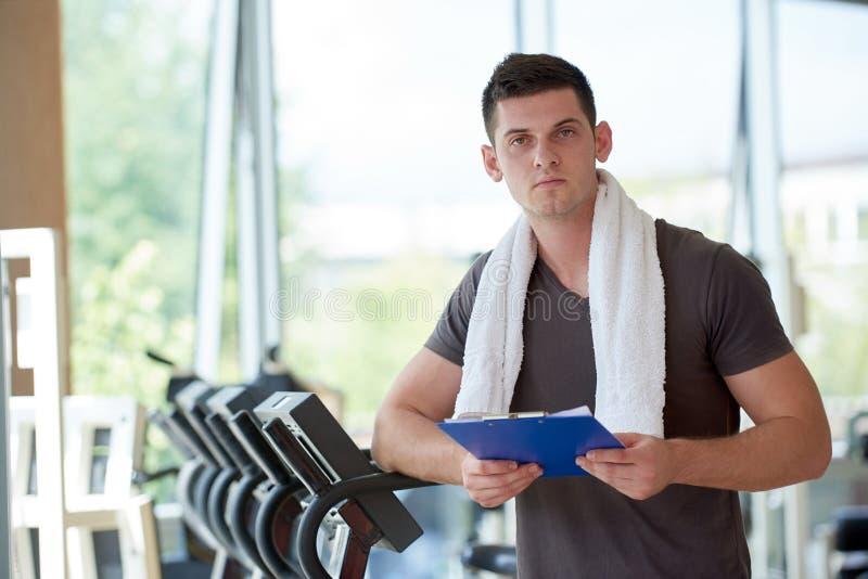 Instrutor com a prancheta que está em um gym brilhante imagem de stock