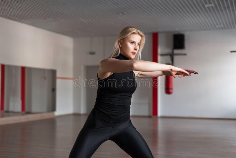 Instrutor da aptidão da jovem mulher em mostras à moda pretas da roupa como manter o equilíbrio estar no gym Menina bonita magro fotos de stock royalty free