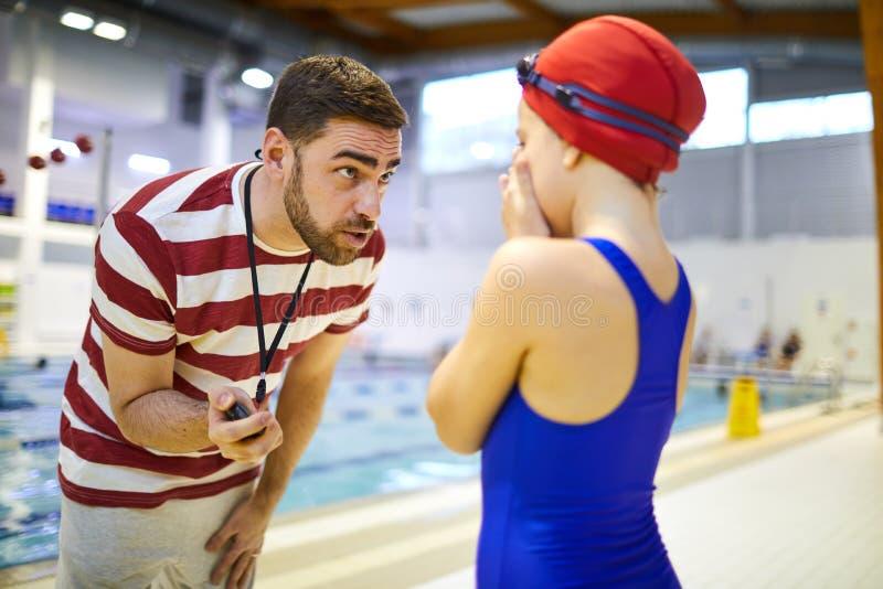 Instrutor da nadada que fala ao atleta imagens de stock royalty free
