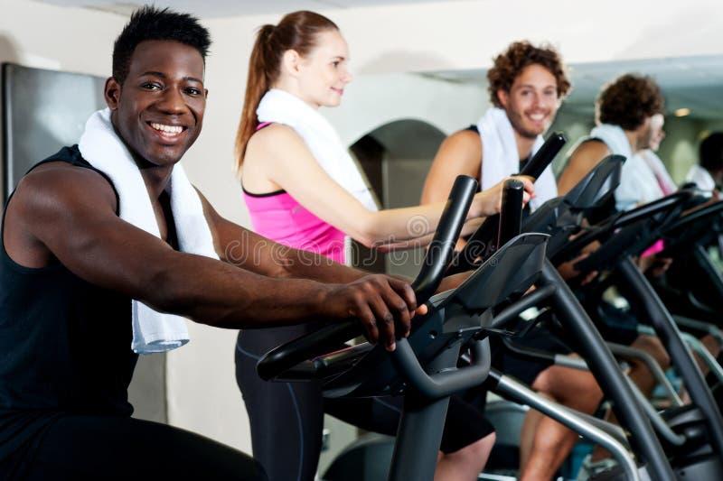 Instrutor do Gym que exercita junto com seus estagiários imagem de stock
