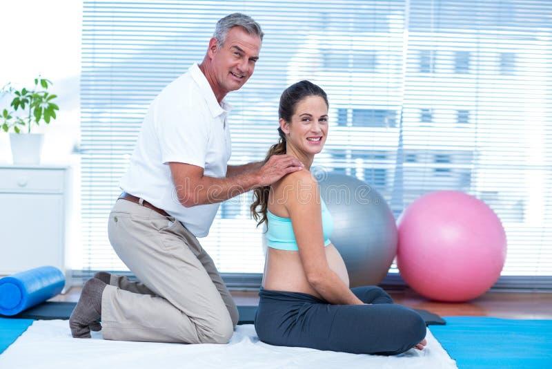 Instrutor do Gym que faz massagens a mulher gravida feliz foto de stock royalty free