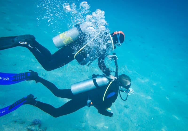 Instrutor do mergulho que mostra o primeiro mergulho na água aberta imagens de stock
