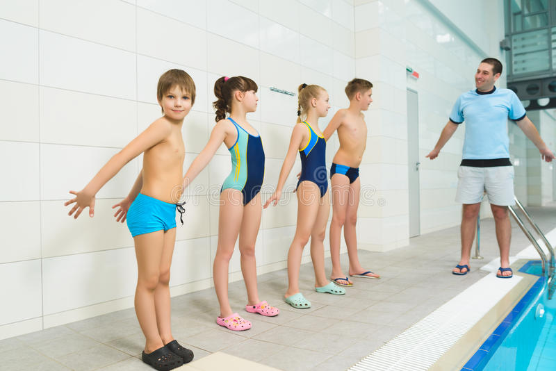 Instrutor e grupo de crianças que fazem exercícios perto de uma piscina foto de stock