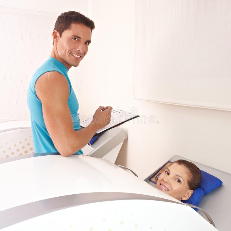 Instrutor e mulher no ozônio da cabine foto de stock