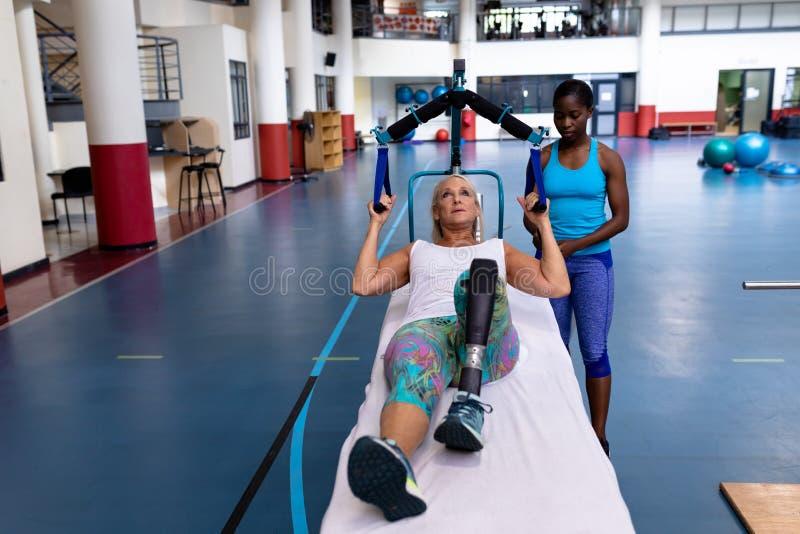 Instrutor fêmea que ajuda à mulher superior ativa deficiente a exercitar no centro de esportes foto de stock