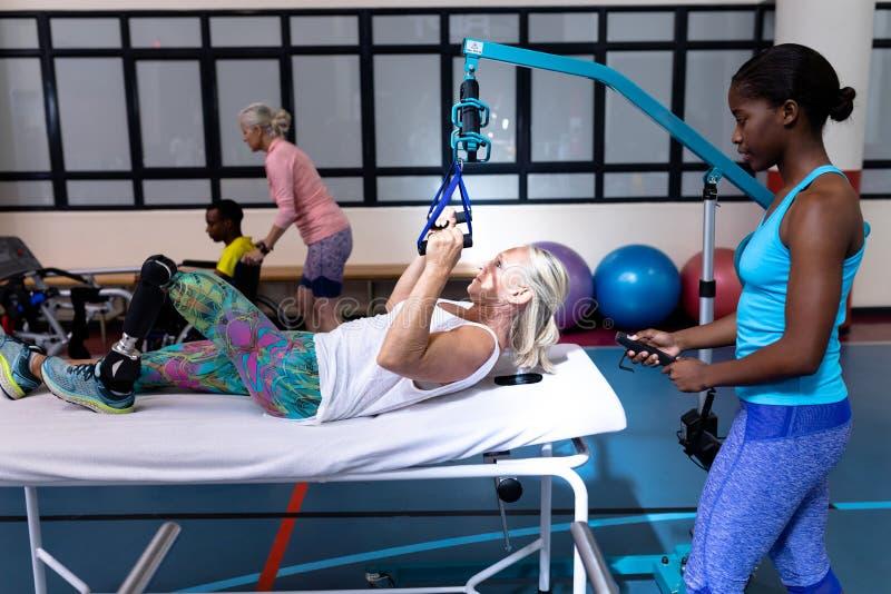 Instrutor fêmea que ajuda à mulher superior ativa deficiente a exercitar no centro de esportes foto de stock royalty free
