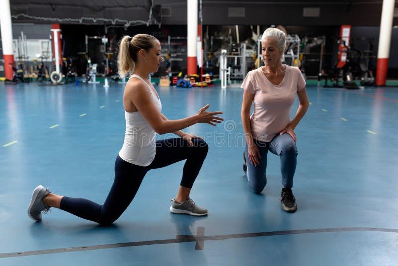 Instrutor fêmea que ajuda à mulher superior ativa no centro de esportes moderno foto de stock royalty free