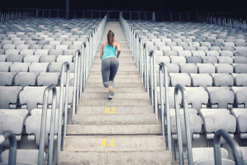 Instrutor fêmea que dá certo em escadas, treinamento da aptidão e fazendo exercícios foto de stock