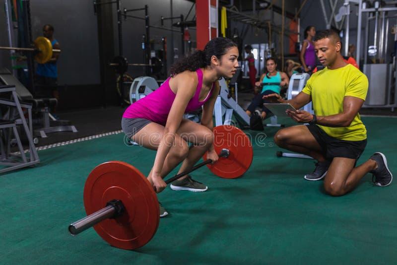 Instrutor masculino que ajuda a atlético fêmea a levantar o barbell no fitness center fotos de stock royalty free