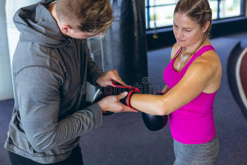 Instrutor masculino que ajuda atlético fêmea a vestir luvas de encaixotamento no fitness center foto de stock royalty free