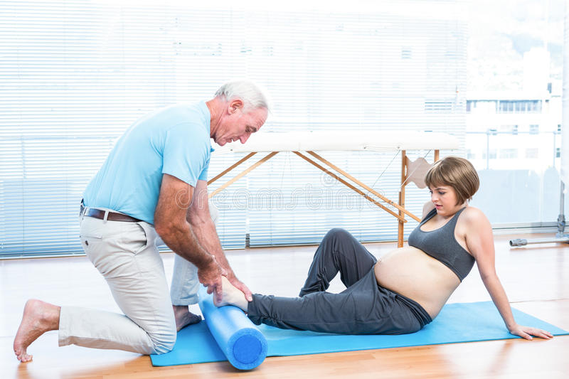 Instrutor masculino que faz massagens o pé da mulher gravida fotografia de stock
