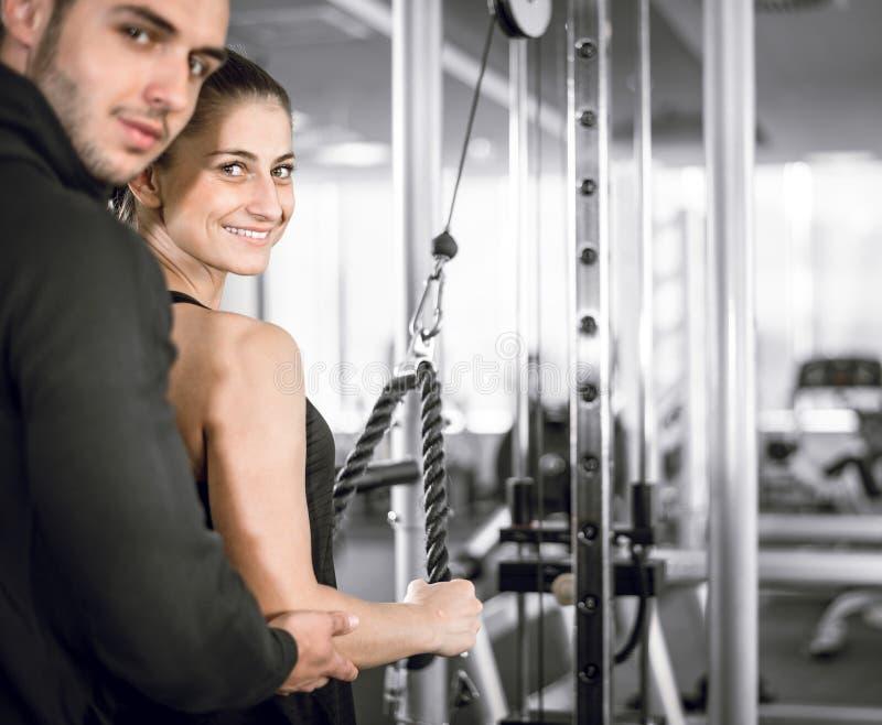 Instrutor pessoal da aptidão com seu cliente no gym fotos de stock
