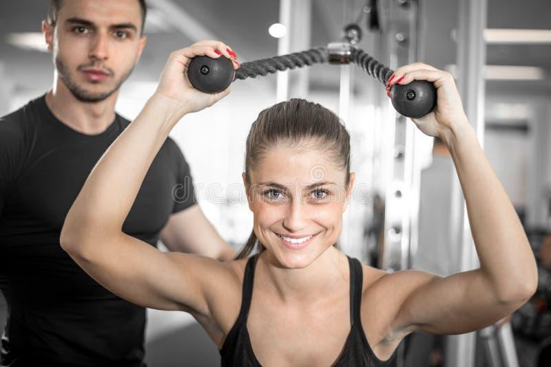 Instrutor pessoal da aptidão com seu cliente no gym imagens de stock royalty free