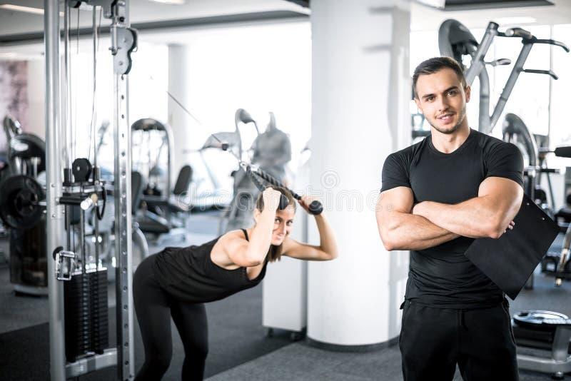 Instrutor pessoal da aptidão com seu cliente no gym foto de stock royalty free