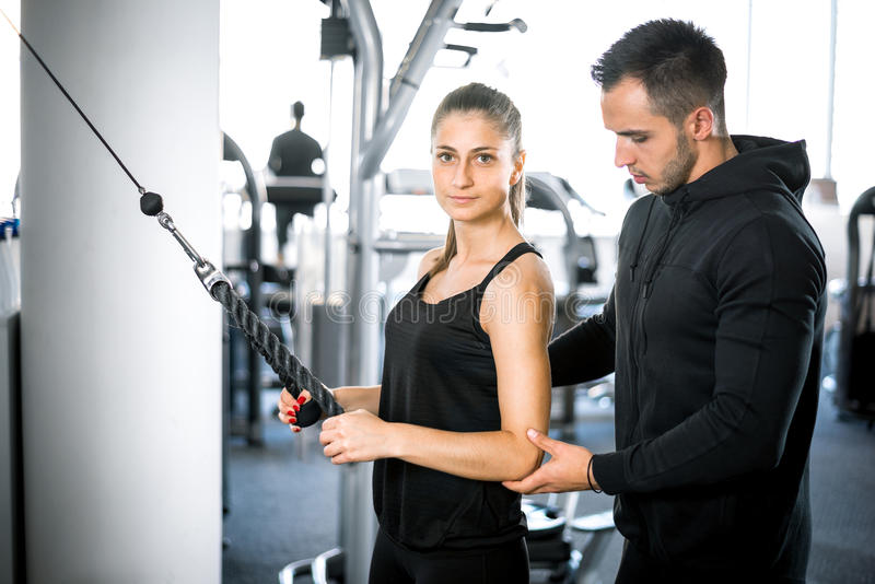 Instrutor pessoal da aptidão com seu cliente no gym imagem de stock