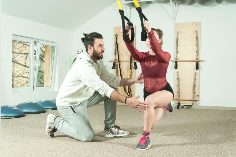 Instrutor pessoal masculino considerável com uma barba que ajuda a menina bonita nova para o exercício aeróbio no gym, foco selet imagem de stock royalty free
