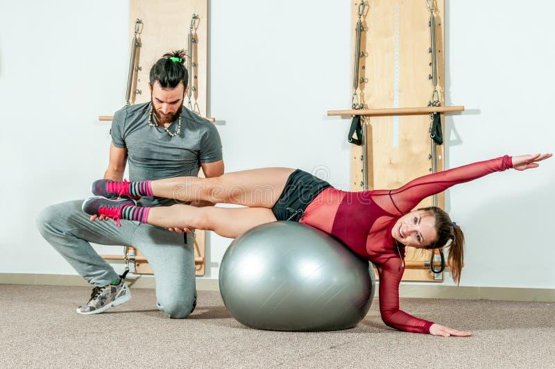Instrutor pessoal masculino considerável da ioga com uma barba que ajuda a menina bonita nova para o exercício aeróbio no gym, fo fotografia de stock royalty free