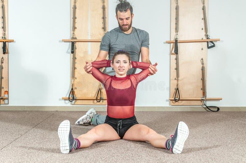 Instrutor pessoal masculino da ioga considerável com uma barba que ajuda a menina nova da aptidão a esticar seus músculos após o  fotos de stock royalty free