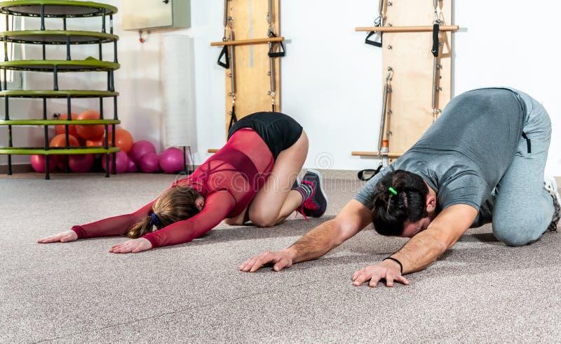 Instrutor pessoal masculino da ioga considerável com uma barba que ajuda a menina nova da aptidão a esticar seus músculos após o  imagem de stock royalty free