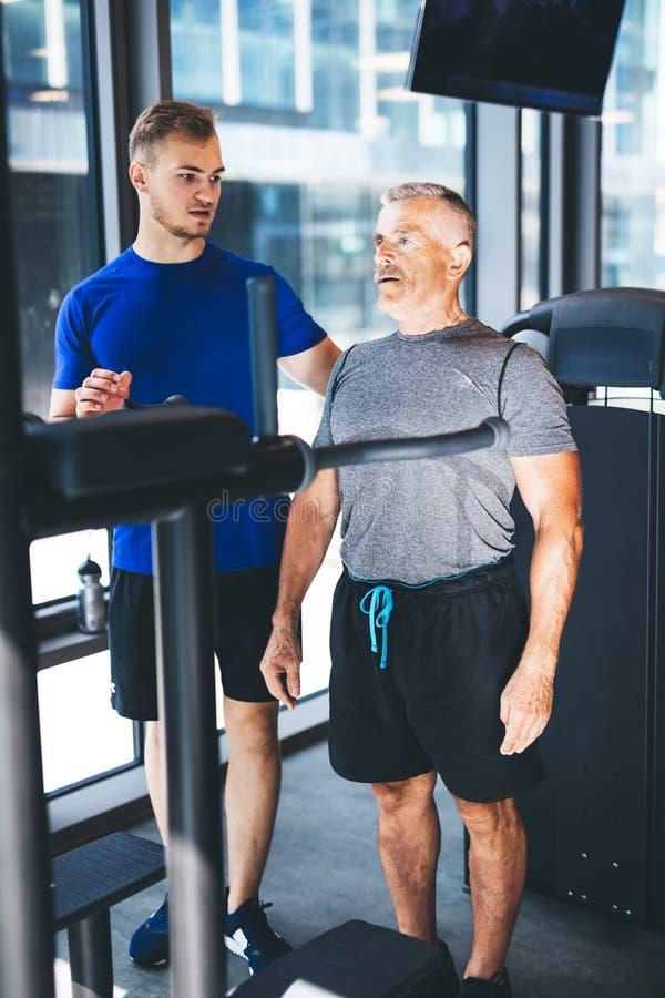 Instrutor pessoal que dá instruções ao homem mais idoso no gym imagens de stock royalty free