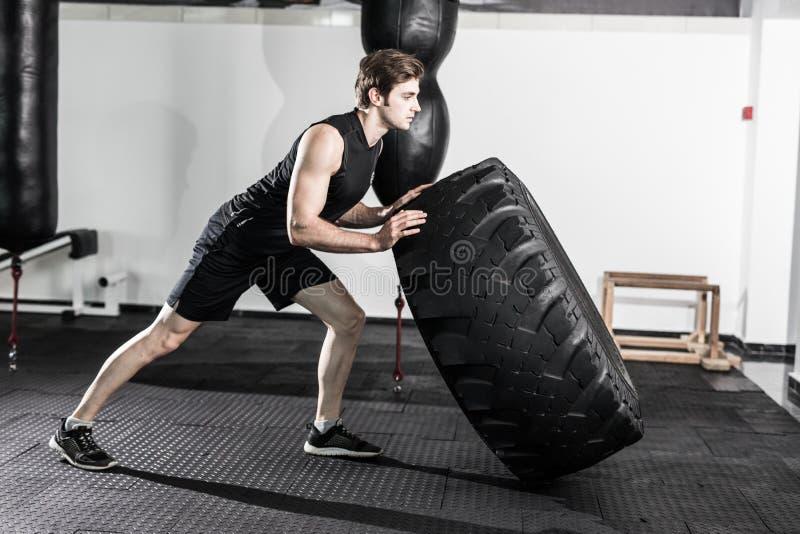 Instrutor pessoal que lança um pneumático em um gym ao instruir um modelo fêmea da aptidão como fazer o exercício imagens de stock royalty free