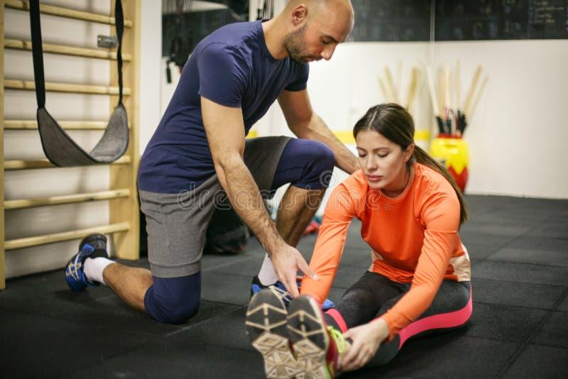 Instrutor pessoal que treina seu cliente no gym imagem de stock