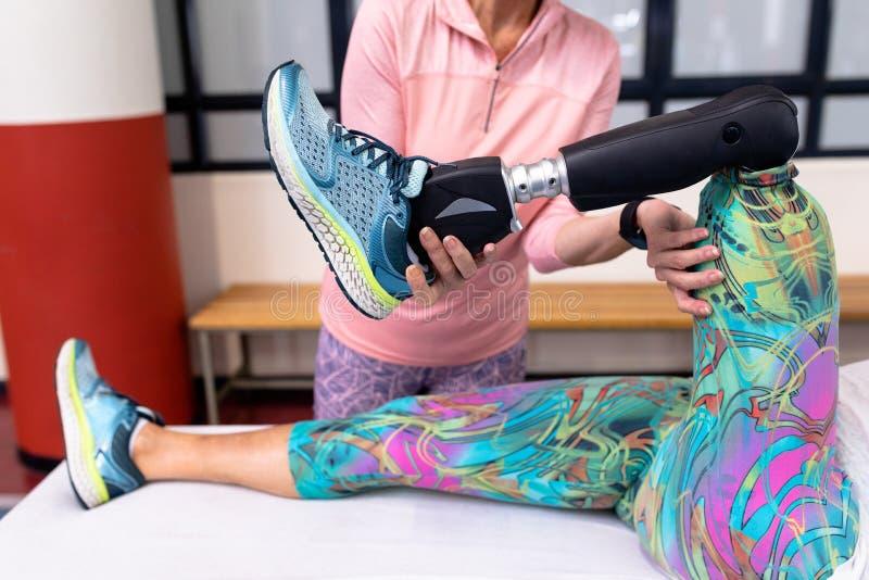 Instrutor que ajuda à mulher superior ativa deficiente a esticar o pé no centro de esportes imagens de stock